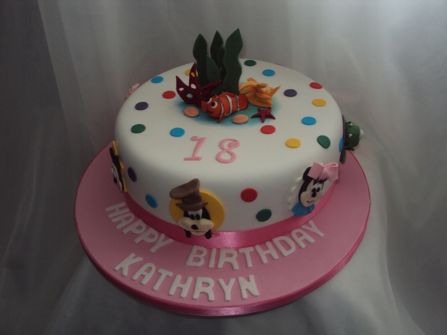 ... several different characters on a multi coloured spotty white cake