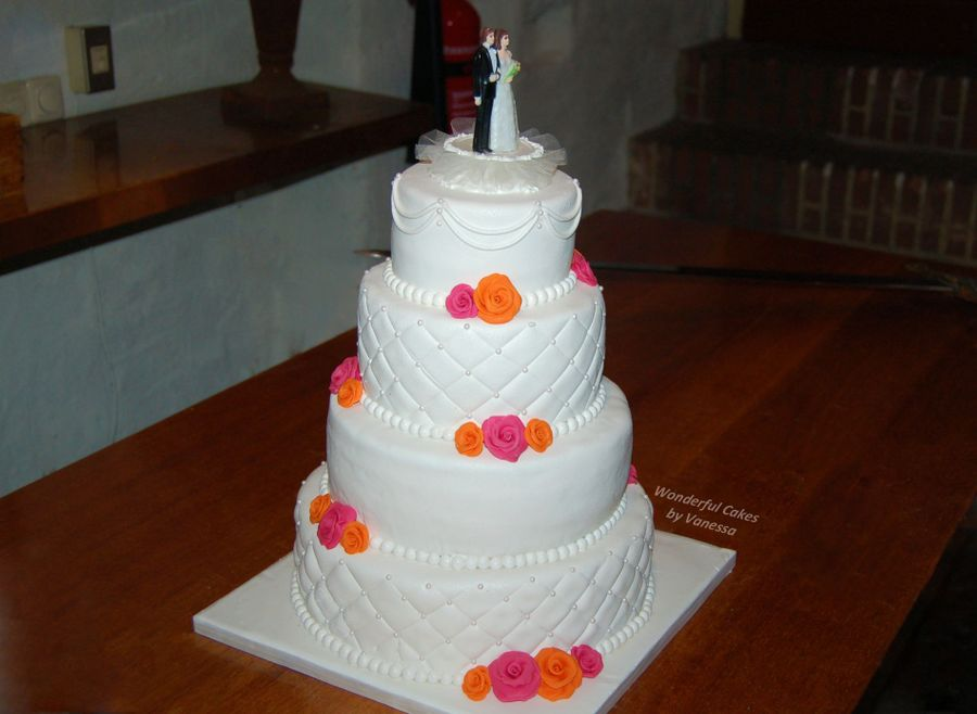 significance of a wedding cake a 4 tier wedding cake with pink and orange roses the cake 19818