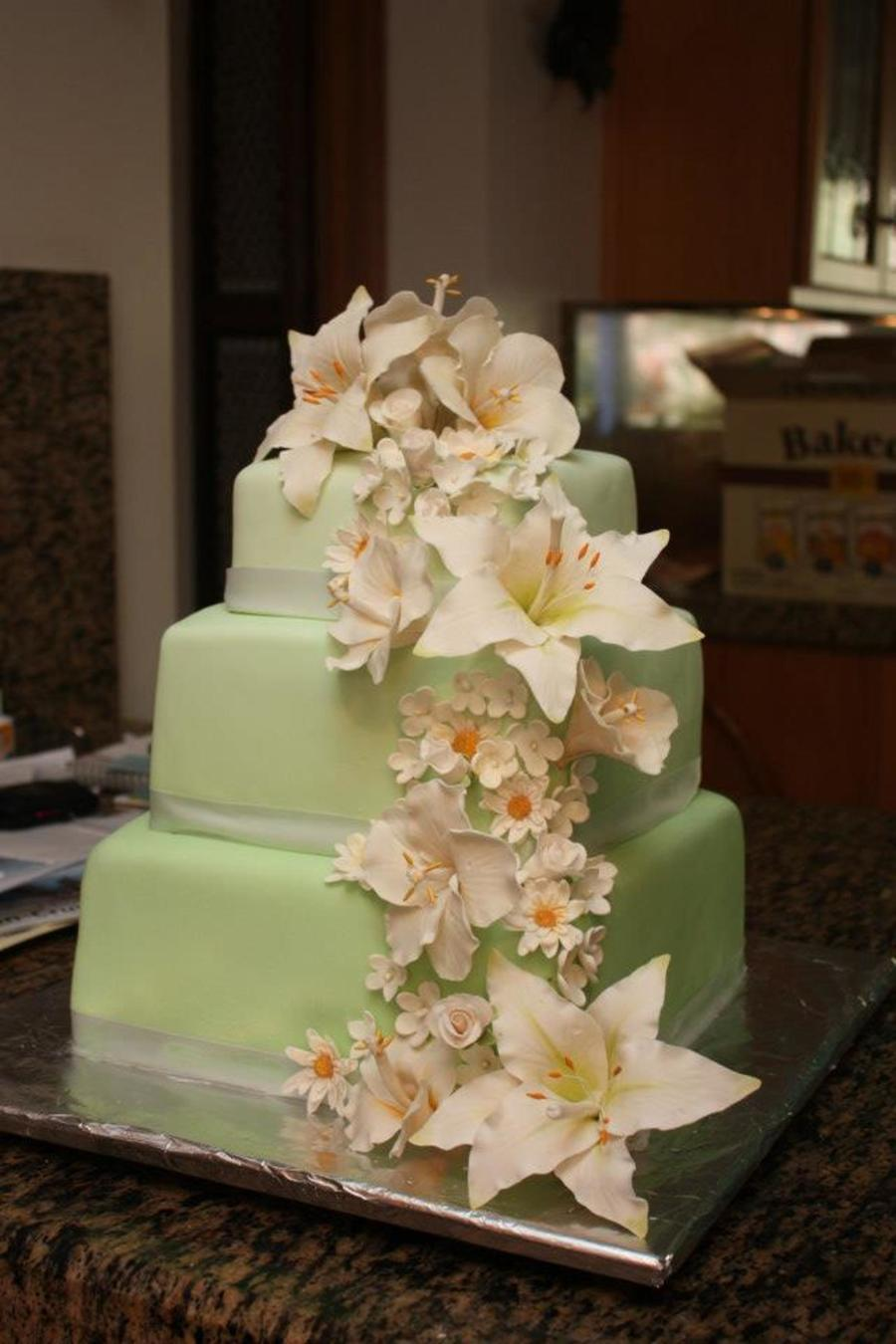 Green Ombre Fondant Tiers With Cascade Of Gum Paste Lilies Hibiscus And Daisies on Cake Central