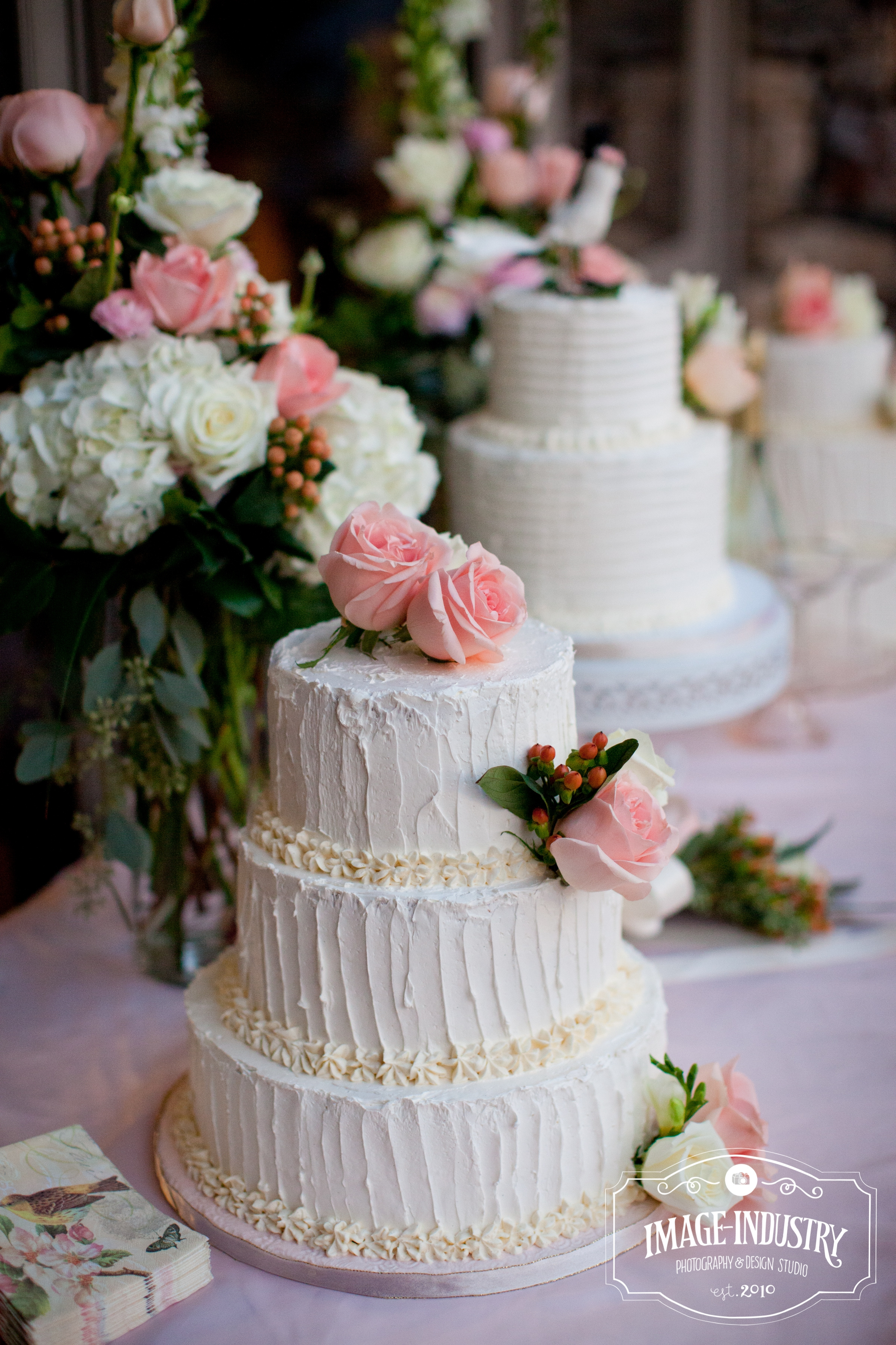trio of butter cream wedding cakes all with a different texture and topped with fresh flowers. Black Bedroom Furniture Sets. Home Design Ideas