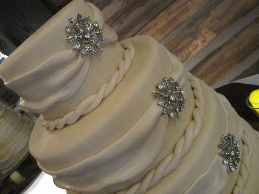 Round 4 Tier Off White Cake With Draped Swag And Brooches