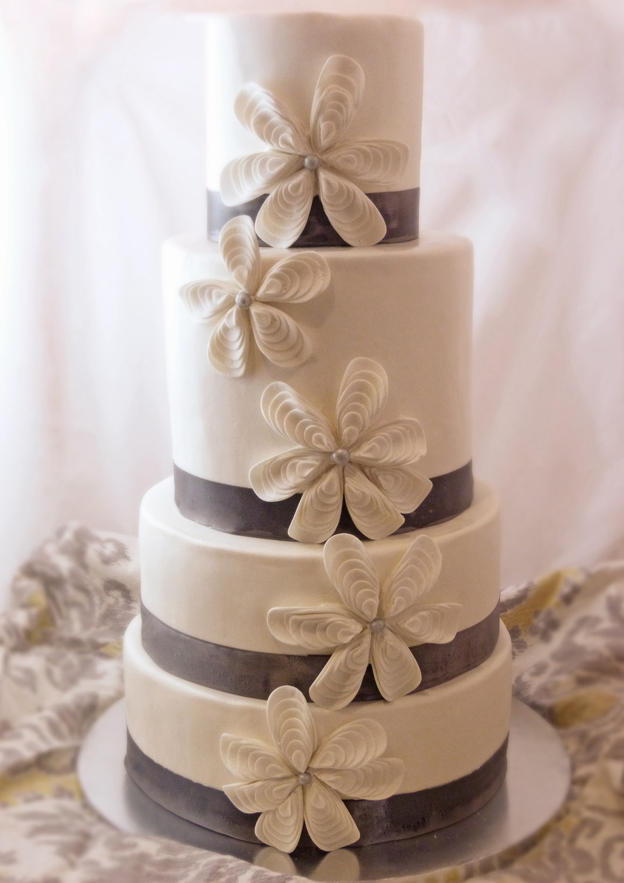 Four Tier Wedding Cake Covered In Ivory Fondant Grey Ribbon And Flowers Created From White Petals Overplayed Various Sizes