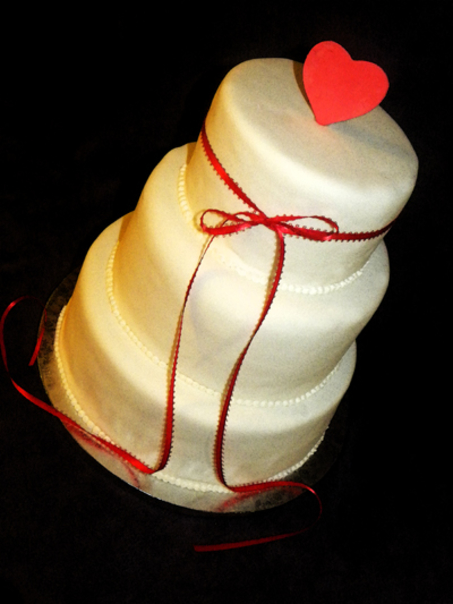 3 Tiers Anniversary Cake Covered On White Fondant With Red Ribbon And Fondant Heart Decorations on Cake Central