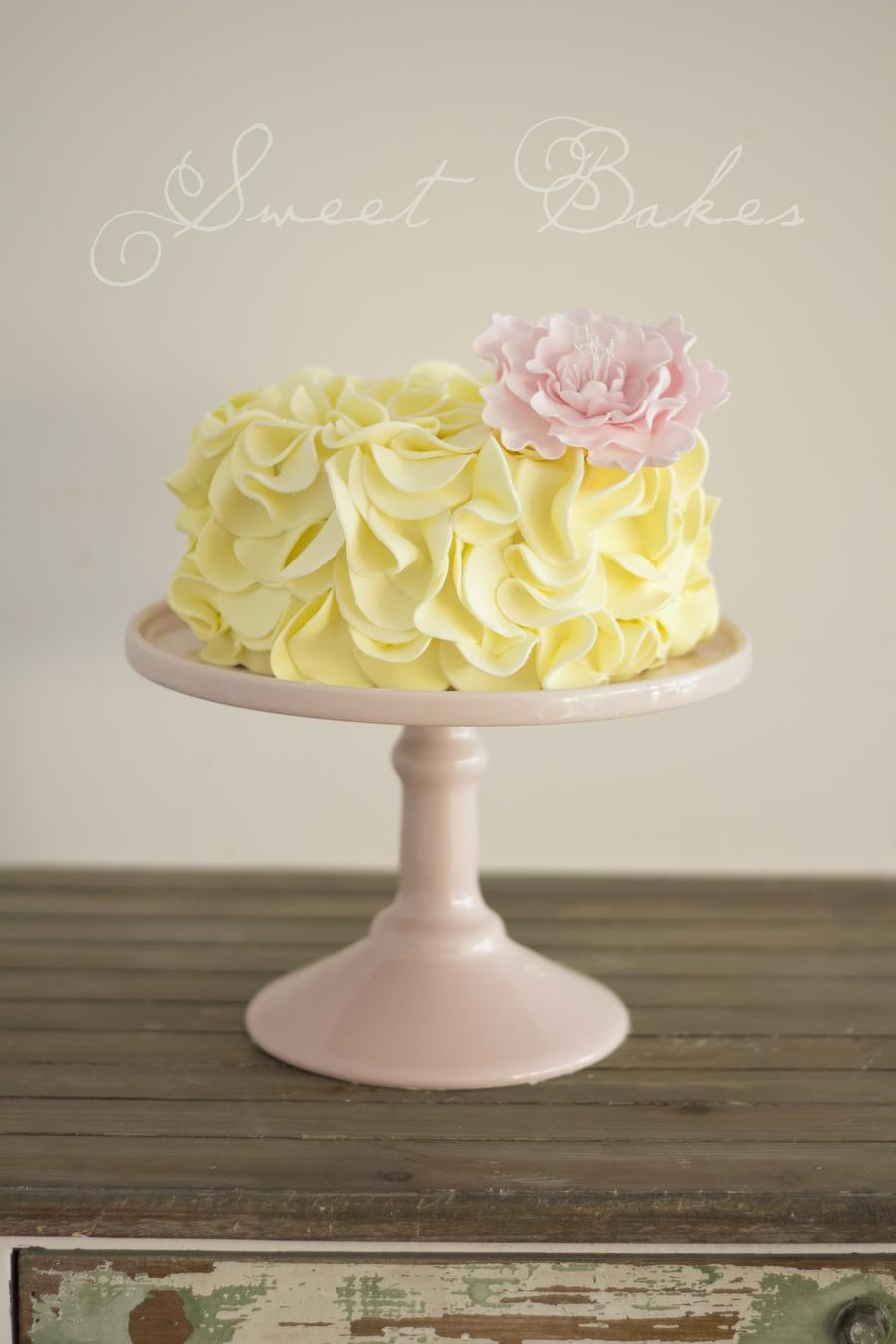 Yellow Ruffle Cake With A Handmade Pink Peony