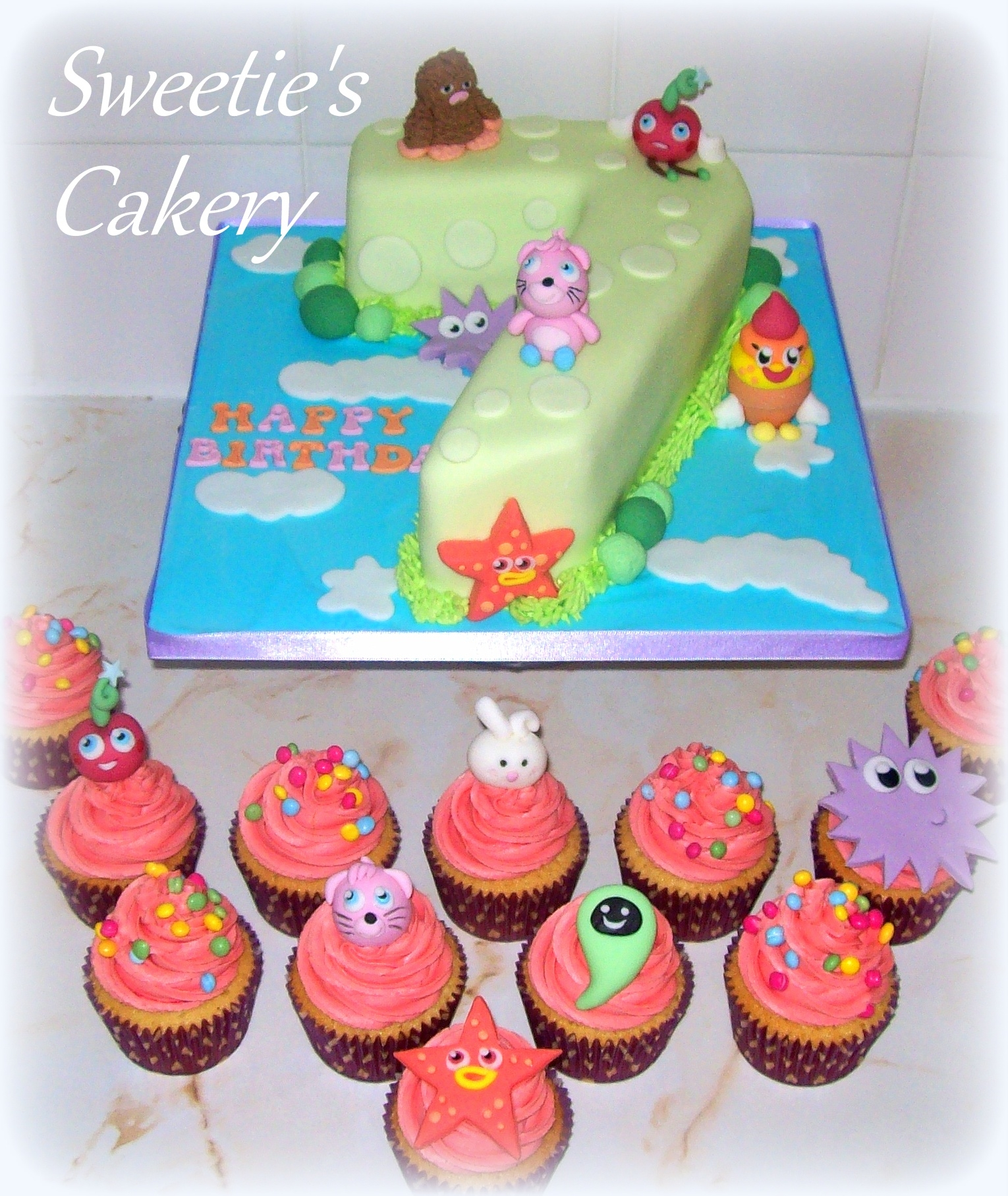 Moshi Monster Themed Green Number 7 Birthday Cake With Matching Pink Cupcakes