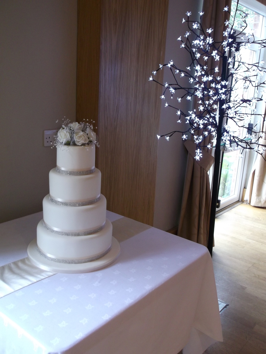 Four tier ivory wedding cake with diamante ribbon and a topper four tier ivory wedding cake with diamante ribbon and a topper with silk flowers and diamante which was provided by the bride x junglespirit Gallery