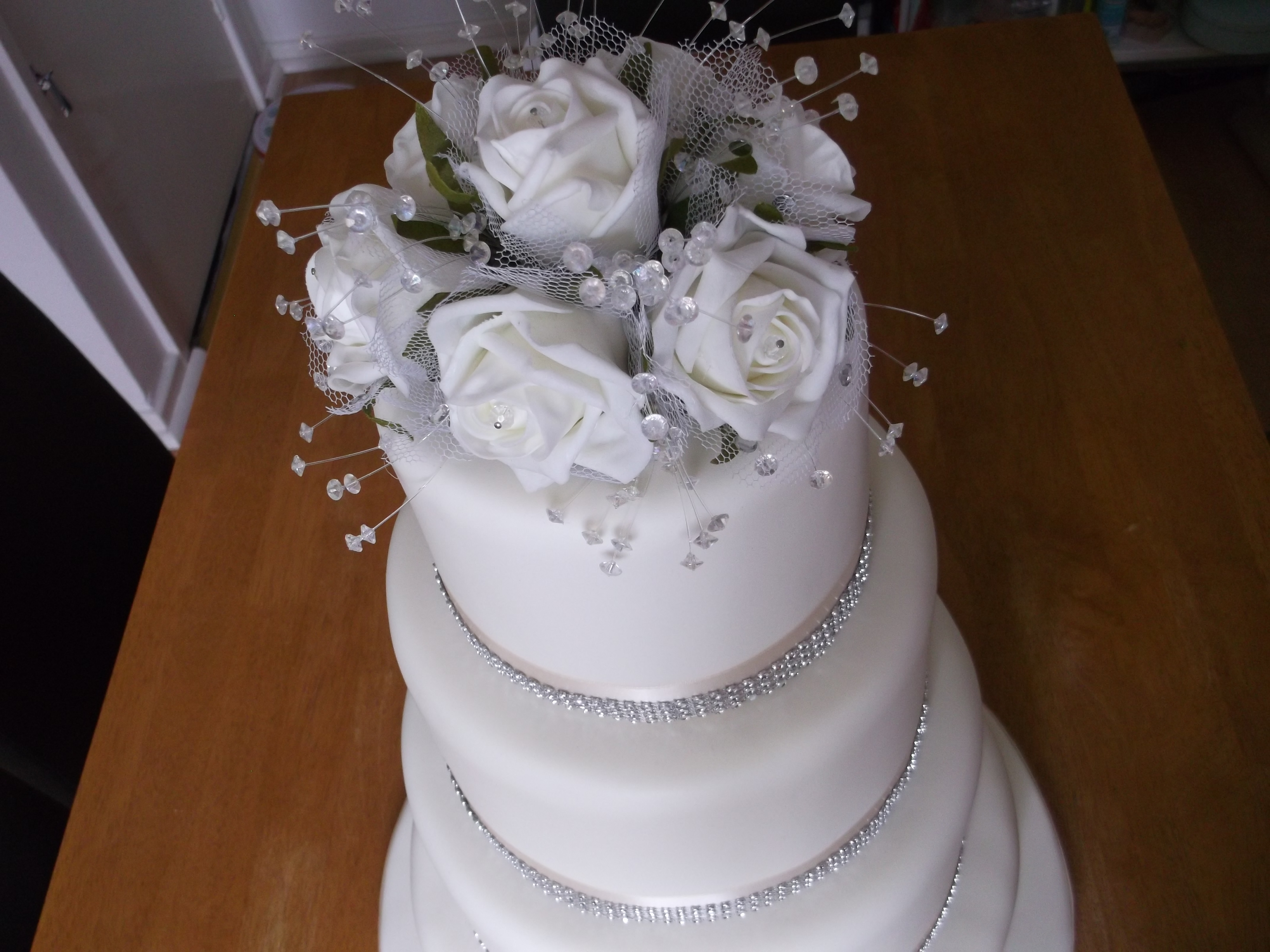 Four Tier Ivory Wedding Cake With Diamante Ribbon And A Topper With