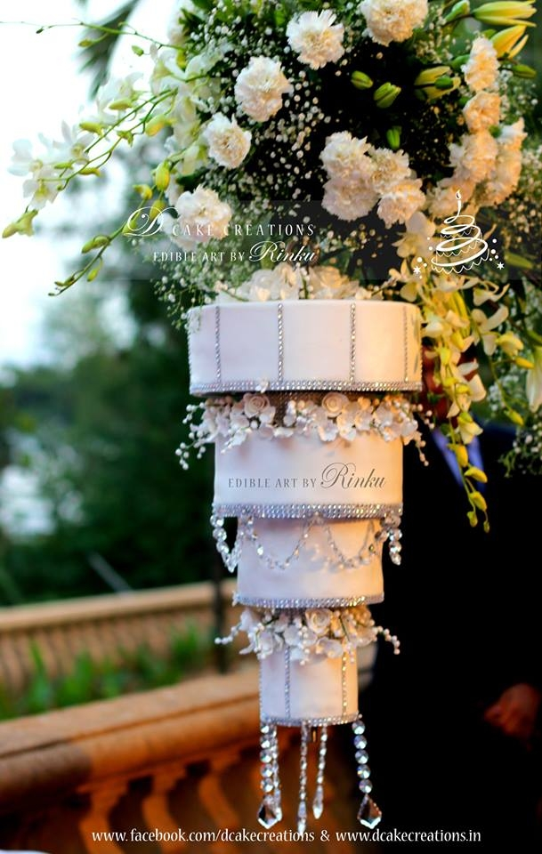Four Tier Chandelier Wedding Cake Hanging Upside Down On A Stand The Was Decorated With Sugar Flowers Silver Studded Ribbons Crystals