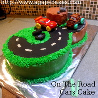 On The Road, Cars Cake White velvet confetti cake iced and decorated with Swiss Merignue Icings, and modeling chocolate. I bought the two cars for my son to play...