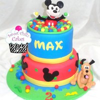Mickey Mouse Clubhouse 2 tiered Mickey Mouse Clubhouse cake with edible Mickey on top and Pluto on bottom and Mickey is playing in a ball pit.