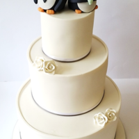 Wedding Cake With Hand Made Penguin Bride And Groom Toppers 3 tier gluten free wedding cake. Handmade mini roses and custom bride and groom penguin toppers.