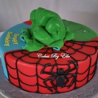 "Super Heroes 12"" White cake w/Peach filling and covered in fondant. Hulk fist is made of rice krispies and cover in fondant."