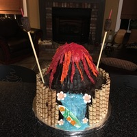 Luau Party   Volcano cake with tiki torches made from fondant with candles inserted.