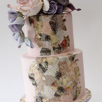 Decoupage Floral  This two tier cake features wafer paper decoupage and metal leaf accents topped with a giant sugar rose, ranunculus, calla lilies,...