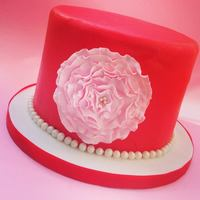 Red And Ruffled Flower A red fondant covered cake with a pink ruffled flower and pearls