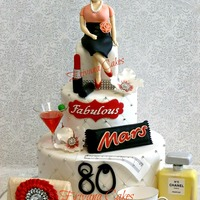 80Th Birthday Cake This cake has this dear mom's favorite things and family stuff adorning the cake. The red lipstick, Mars bar, wine glass, purse, No 5...