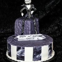 Jack Skellington Birthday Cake The cake has strips of white and marbled fondant. The top is covered in stone textured fondant. Jack is hand made from gum paste and...
