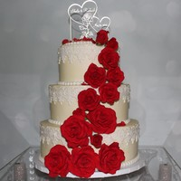 Vintage Ivory, Lace And Red Roses Wedding Cake 3 tier cake with ivory buttercream, white fondant lace and red roses.