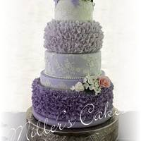 Ruffles And Lace In Dusky Purple Ombre' 5 tiered wedding cake covered in purple ombre fondant, and decked out in fondant ruffles and Cake Lace. Gum Paste flowers added: pink,...