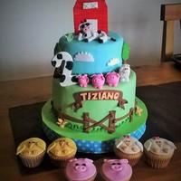 Tizi Farm Cake Two tier cake, with a very cool cow and a farm animals cupcakes