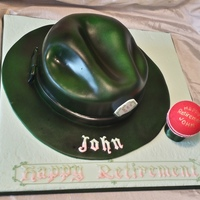 Fedora Hat And Cricket Ball Retirement Cake  Only my second carved cake !!! A dark green Fedora hat air brushed with Holly Green liquid colour. The rim and the hat ribbon are modelling...