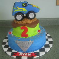 Monster Jam Cake covered in buttercream with fondant accents. Truck is rk treats covered with fondant.