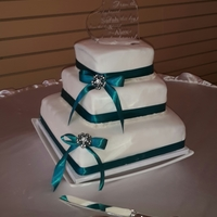Stacked Wedding Cake The bride wanted teal colored cake on the inside with almond buttercream and white chocolate ganache. It is covered in vanilla fondant with...