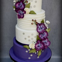 Plum Crazy Plum and white wedding cake with sugar orchids, white roses and silver metallic polka dots. The second photo is the cake setup at the venue...
