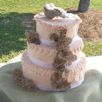 Love Birds Cake Peachy Pink Buttercream Icing with burlap flowers and burlap lovebirds sitting on the top tier. Cake is a dummy cake for show only.