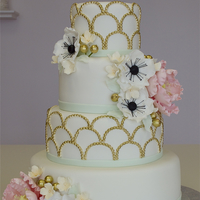 1920's Fondant Wedding Cake   4 tier white fondant wedding cake with gold painted scalloped pearl design and lots of sugar flowers