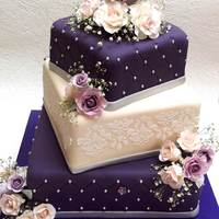 Purple And Cream Wedding Cake With Roses A 3 tier square wedding cake with gumpaste roses, stencilling and quilting.