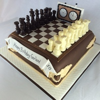 50Th Anniversary Chess Cake 50th Anniversary birthday cake with chocolate molded chess pieces, gumpaste timer and fondant adornments. Everything on the cake was edible...