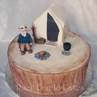 "Mountain Main Camping Tree Stump Cake 12"" round tree stump with cake tent and gumpaste figures."