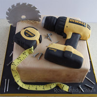 "Tool Cake 10"" square cake to look like a piece of wood. RKT drill and tape measure. Gumpaste saw, tape, nails, etc. All edible."
