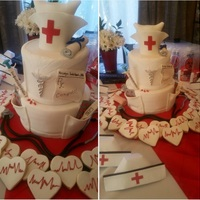 Rn Graduation Cake   Both tiers covered in ganache and fondant. Nursing tools are all gumpaste. EKG sugar cookies covered in fondant.