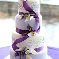 Lavender And White Sugar Calla Lily Wedding Cake Four tier wedding cake covered in fondant, freehand piped in lavender royal icing and finished with purple ribbon and 25 sugar calla lilies...