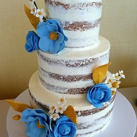 Naked Cake With Blue And Gold Florals Rustic bridal shower cake with gumpaste flowers in blue and gold to match the shower invitation.