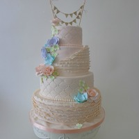Pastel Wedding Cake The couple wanted an ivory wedding cake with ruffles and pastel flowers. It turned out just the way they wanted.