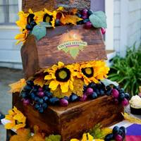 "Vintage Festival Crates  Crooked cake with painted on buttercream to achieve the ""old wood"" look. Logo on middle tier was an edible image. After delivery..."