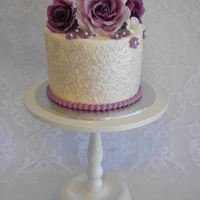 "Lace And Roses This is a 6"" vanilla cake with Oreo buttercream filling. It is covered in buttercream and wrapped with edible lace. Roses are made..."