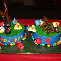 Angry Birds Cake   Cake is covered with butter cream. The birds are made with marshmallow fondant and the blocks/sling shot are all made with tootsie rolls.