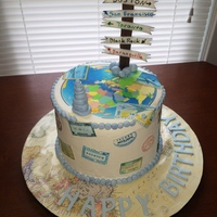 Travel Cake Double barrel, vanilla bean cake with chocolate ganache filling. Buttercream icing, edible printed sugar sheets, fondant cairn and fondant...