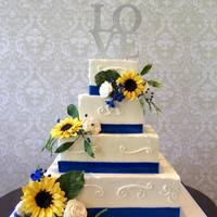 Wedding Cake/ Sunflowers,roses,and Blue Accents.   Square buttercream with all sugar flowers.