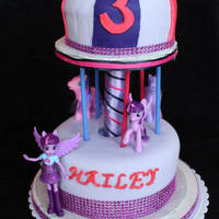 Twilight Sparkle Carousel Cake  The stand/support for this is a home made stand made from plywood and pvc pipe. I simply hot glue gun the ribbon to the stand and it is...