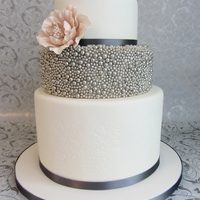 Moden Wedding 3 tiered wedding cake with embossed bottom and silver pearls applied with piping gel.