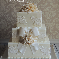 Vintage Lace And Ribbon Rose Wedding   Buttercream iced tiers with fondant ribbon roses, bow and lace onlays.