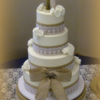 Rustic Charm This wedding cake consists of four tiers of vanilla and strawberry cake, iced in vanilla buttercream and finished with faux burlap and lace...