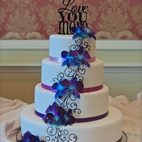Ombre Purple And Blue Orchids   Ombre purple ribbon, black royal icing piping and fresh blue orchids.