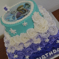 Frozen Cake 2 tiered Frozen themed cake with Anna & Elsa transfer, purple, white & teal ombre rosettes and snowflakes