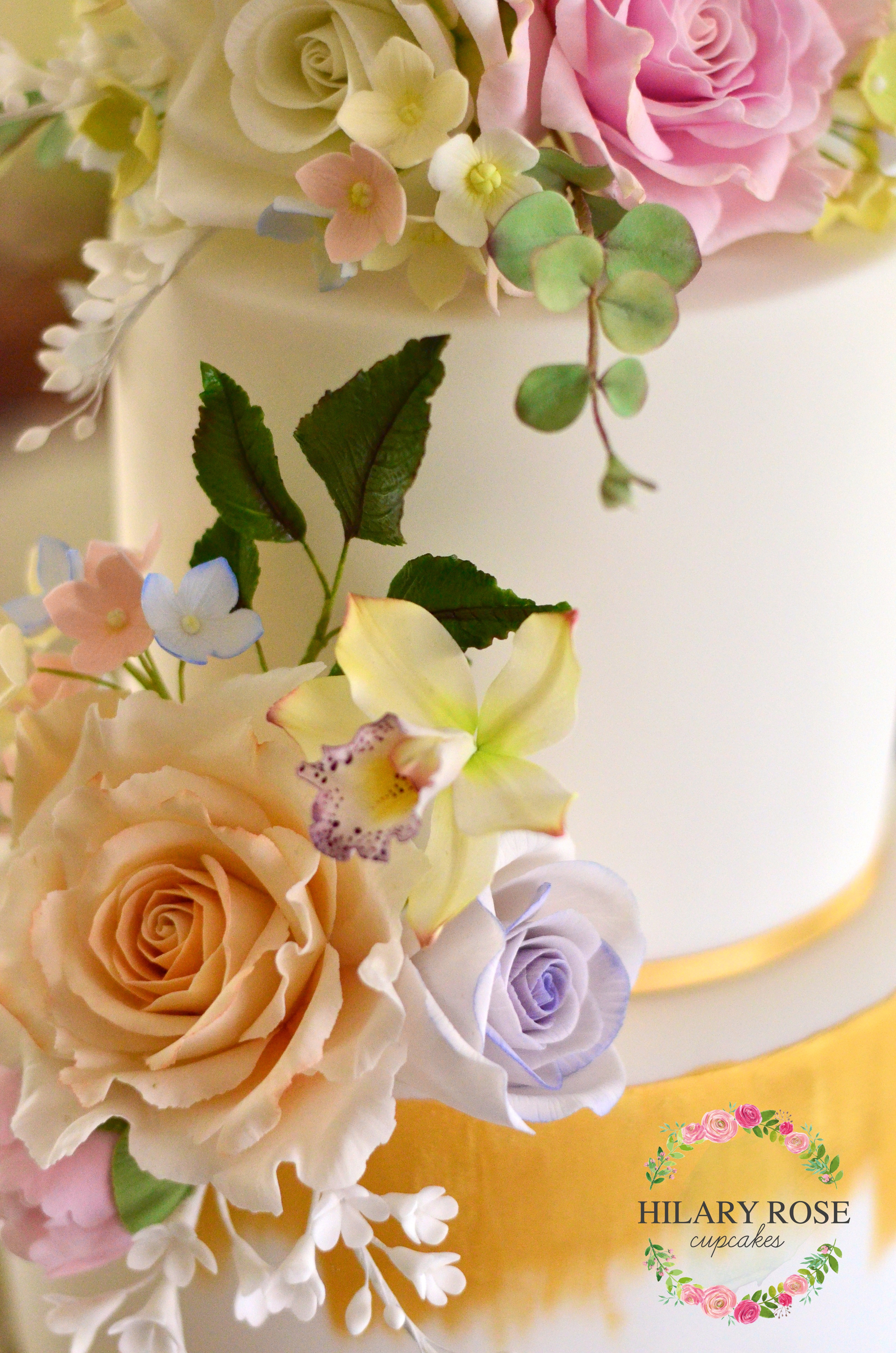 Summer Wedding A three tier wedding cake with gum paste flowers and gold painted embellishments